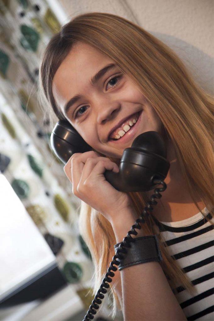 Pige besøger Tidens Samlings 1950'er stue, hun taler i drejeskivetelefonen fra 50'erne på museet Tidens Samling, museum for klæder, form og bolig i det 20. århundrede, kultur i Odense