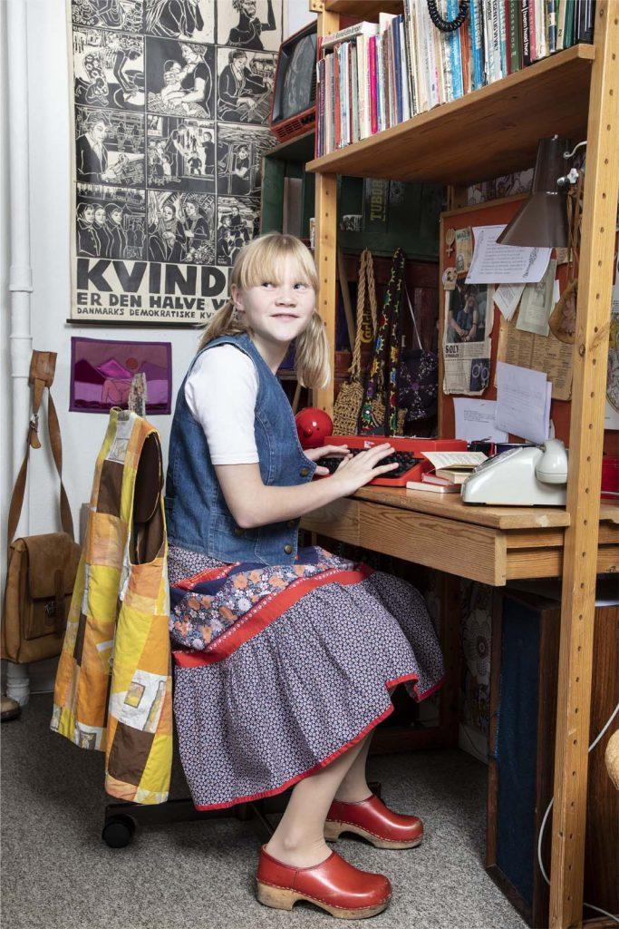 Pige ved skrivebord i Tidens Samlings 1970'er-stue, besøg i 70'erne med 70'er-tøj, skrivemaskine, patchwork, røde træsko, kvindekamp på musum for klæder, form og bolig i det 20. århundrede, kultur for skoler i Odense