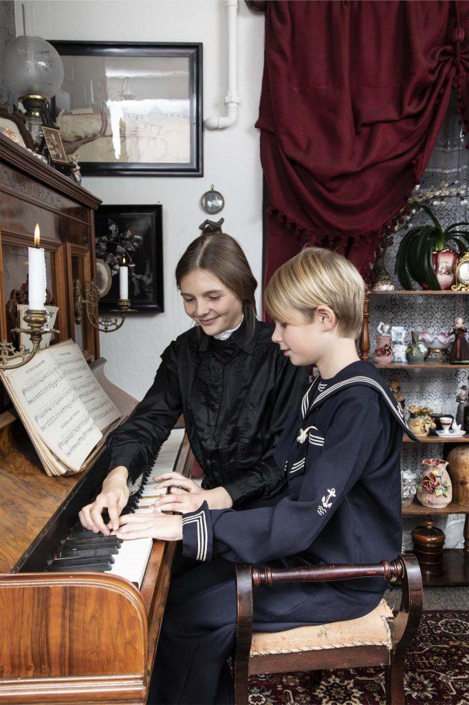 Modelbillede af dreng og pige i Tidens Samlings 1900-stue iført lang sort kjole og matrostøj. Børnene spiller klaver, pigen lærer drengen at spille på Tidens Samling, museum for klæder form og bolig i det 20. århundrede