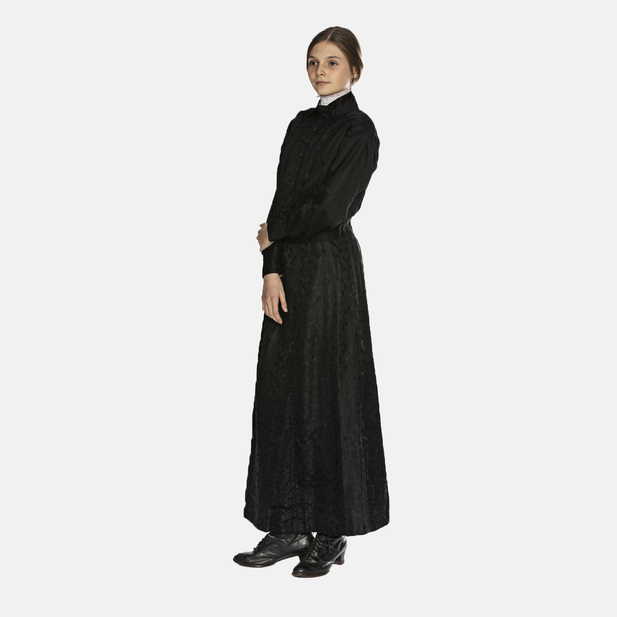 Pige i lang, sort, tilknappet kjole fra 1910'erne, læs om moden i 1910'erne, originalt tøj fra Tidens Samling, museum for klæder, form og bolig i det 20. århundrede, Kulturmaskinen, Farvergården, Brandts Klædefabrik, Odense