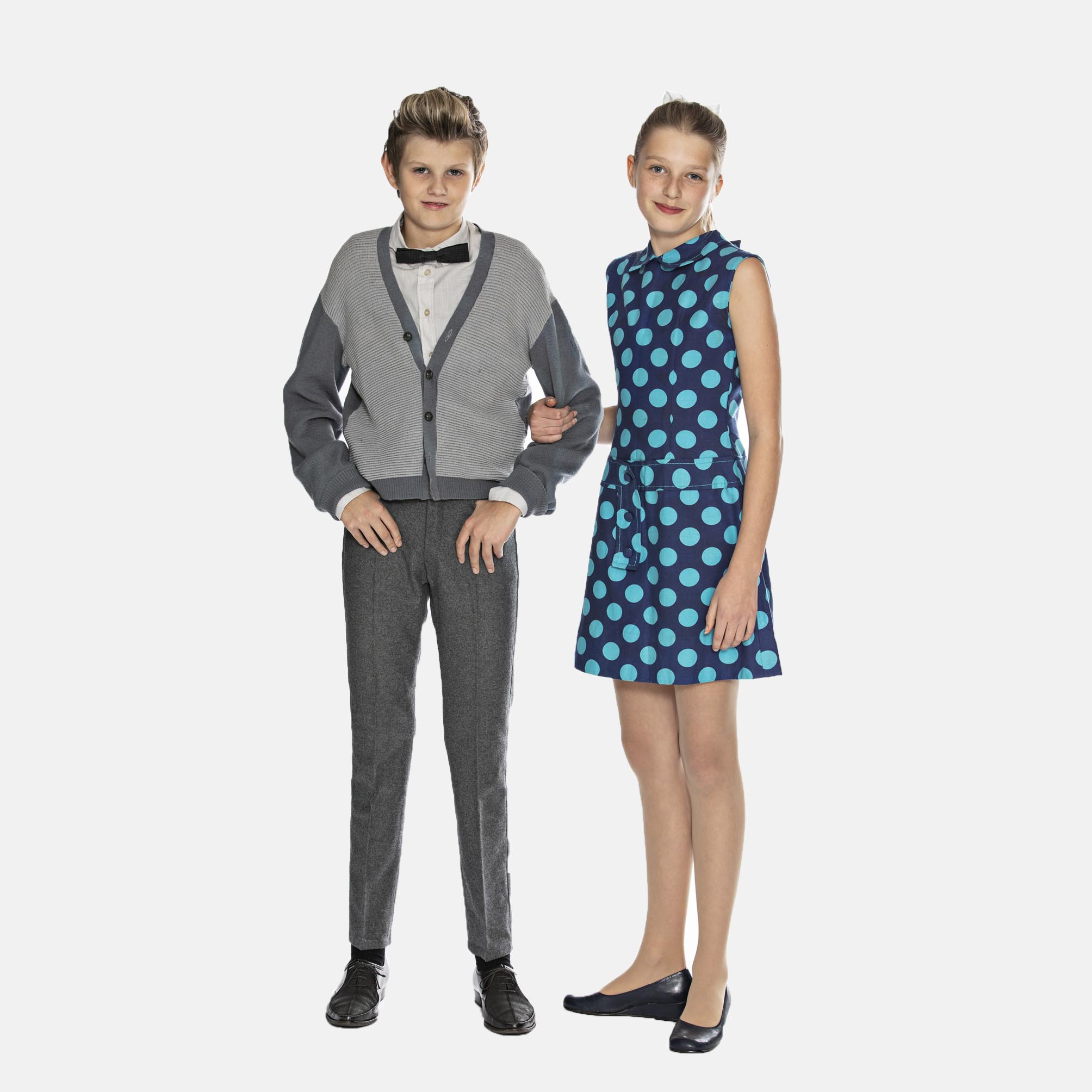 Dreng fra 60'erne med slikhår, butterfly, strikke vest, smalle grå bukser og 60'er-pige med blåmønstret kort kjole, bare ben og sløjfe i håret, læs mere om moden fra 1960'erne, originalt tøj fra museet Tidens Samling, museum for klæder, form og bolig i det 20. århundrede, Kulturmaskinen, Farvergården, Brandts Klædefabrik, Odense