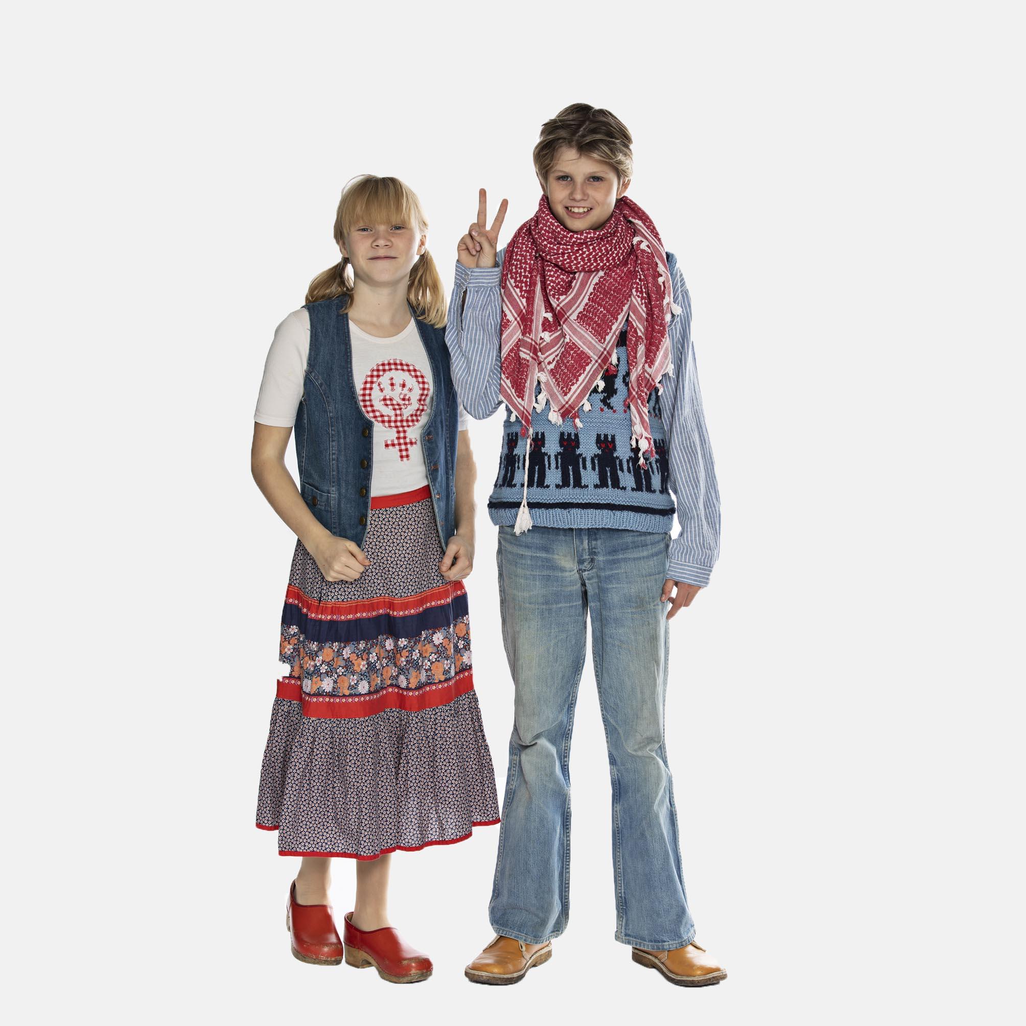 Dreng fra 1970'erne med hjemmestrikket sweater, hvidt og rødt partisanertørklæde, vidde cowboybukser, fodformede brune sko og peace-tegn, med 70'er-pige i lang nederdel i farver og mønstre, peace-t-shirt, cowboyvest, røde træsko og rottehaler, læs om moden i 1970'erne, originalt tøj fra museet Tidens Samling, museum for klæder, form og bolig i det 20. århundrede, Kulturmaskinen, Farvergården, Brandts Klædefabrik, Odense