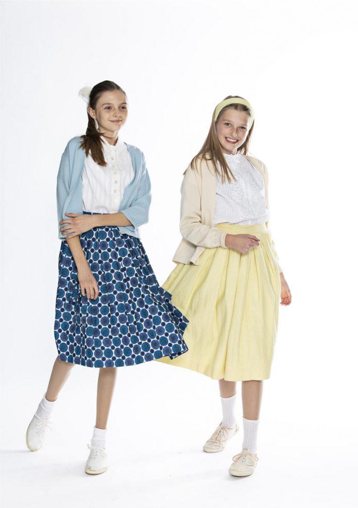50'er-piger i strutskørter, den ene med blåmønstret nederdel, hvid bluse og lyseblå cardigan, lange hvide strømper, hvide lærredssko og sløjfe i håret, den anden med gul nederdel, hvid bluse, lysegul cardigan og lysegult hårbånd, originalt tøj fra 1900-tallet fra museet Tidens Samling, museum for klæder, form og bolig i det 20. århundrede, Kulturmaskinen, Farvergården, Brandts Klædefabrik, Odense
