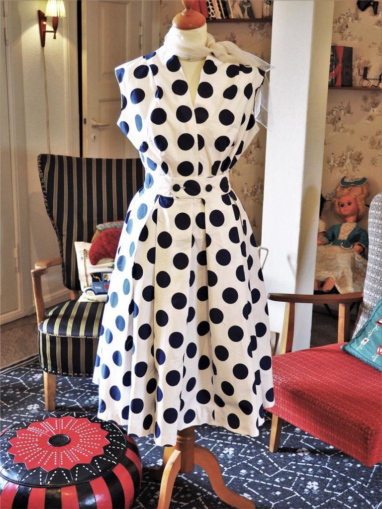 Hvid kjole med mærkeblå bomber, smal talje og strutskørt, læs om moden i 50'erne, originalt tøj fra 1900-tallet fra museet Tidens Samling, museum for klæder, form og bolig i det 20. århundrede, Kulturmaskinen, Farvergården, Brandts Klædefabrik, Odense