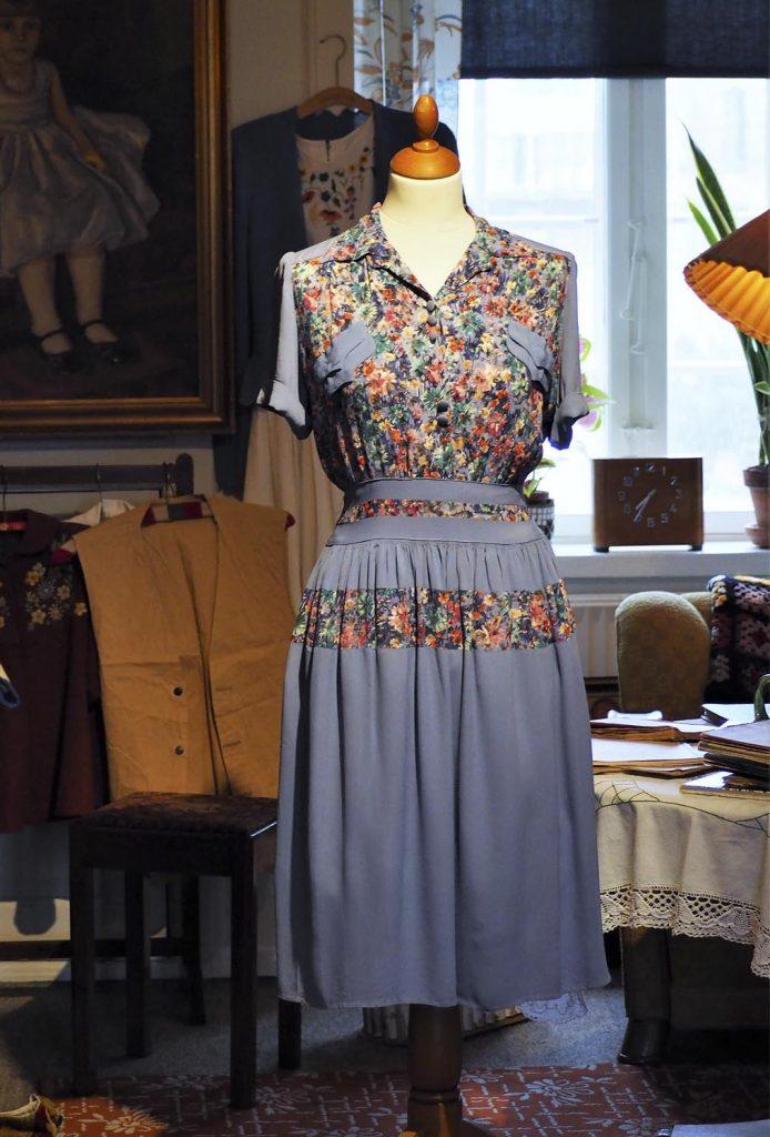 Lilla og blomstret kjole lavet af genbrugte andre kjoler fra under 2. verdenskrig i 1940'erne, meget stof blev genbrugt under krigen, originalt tøj fra museet Tidens Samling, museum for klæder, form og bolig i det 20. århundrede, Kulturmaskinen, Farvergården, Brandts Klædefabrik, Odense