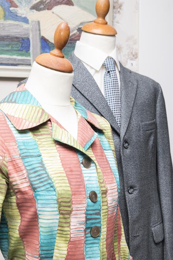 Kvinde og herremode fra 1950'erne, mønstret og flerfarvet jakke til kvinder, gråt jakkesæt med blåt slips til mænd, læs om moden i 1950'erne, originalt tøj fra 1900-tallet fra museet Tidens Samling, museum for klæder, form og bolig i det 20. århundrede, Kulturmaskinen, Farvergården, Brandts Klædefabrik, Odense