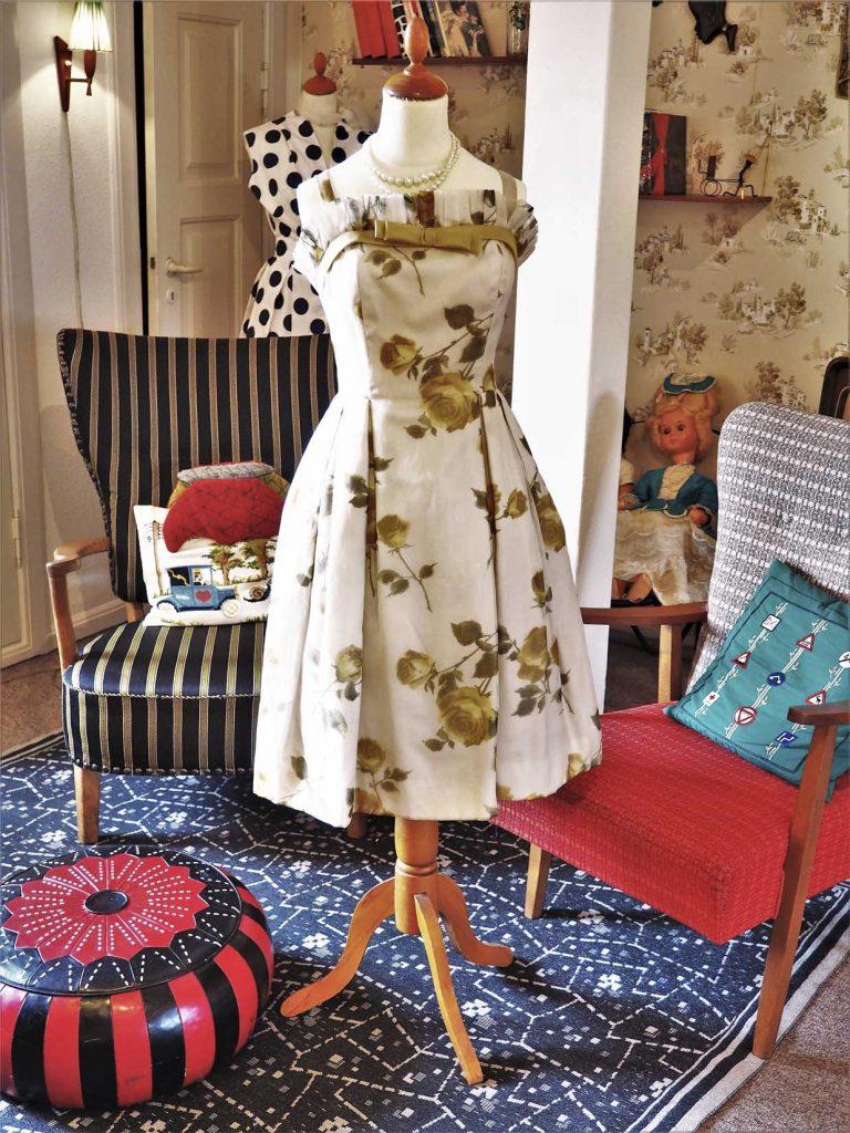 Blomstret kjole fra 1950'erne med smal talje og plisseret skørt, læs om moden i 50'erne, originalt tøj fra 1900-tallet fra museet Tidens Samling, museum for klæder, form og bolig i det 20. århundrede, Kulturmaskinen, Farvergården, Brandts Klædefabrik, Odense