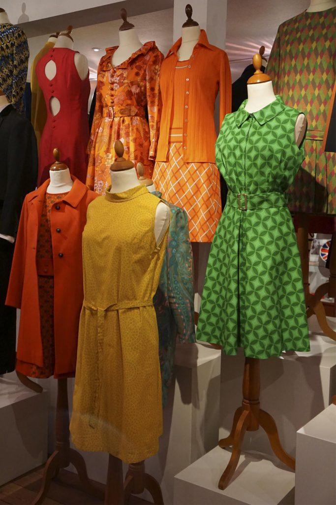 60'er-kjoler fra særudstillingen Ung i 60'erne, gul kjole i psykedelisk mønster og a-snit, grøndmønstret kjole med strutskørt, orange uldfrakke, orange kjole, læs mere om moden fra 1960'erne, originalt tøj fra museet Tidens Samling, museum for klæder, form og bolig i det 20. århundrede, Kulturmaskinen, Farvergården, Brandts Klædefabrik, Odense