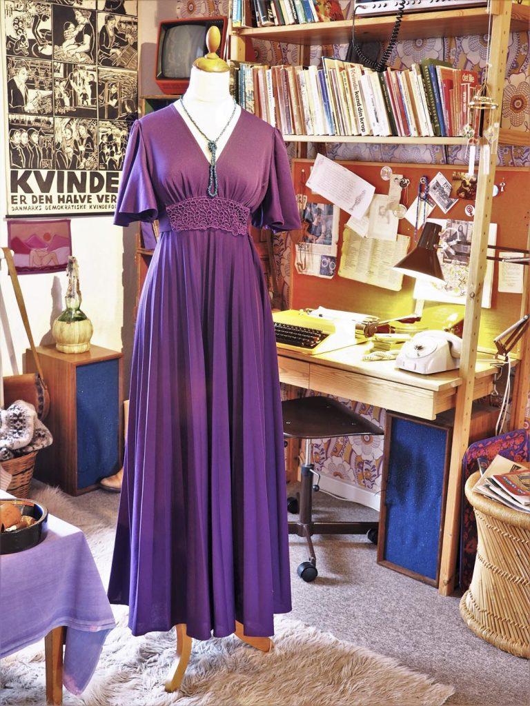 Lilla lang kjole med v-snit, 70'er-stue, 1970'erne, læs om moden i 1970'erne, originalt tøj fra museet Tidens Samling, museum for klæder, form og bolig i det 20. århundrede, Kulturmaskinen, Farvergården, Brandts Klædefabrik, Odense