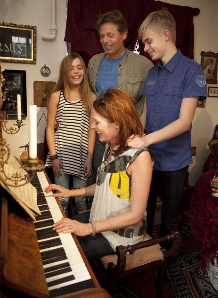 Familie samles om klaveret i museet Tidens Samlings stue indrettet med originale møbler og genstande fra 1900-1919, hvor mor spiller på klaveret